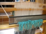 The warp threaded through pattern and ground heddles, then through the reed.