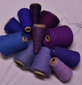 Purple and blue yarn on white background